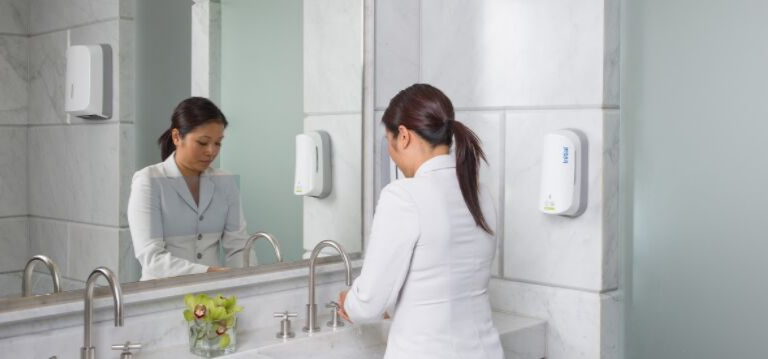 Woman washign her hands using bio-enzyme soap from initial hygiene soap dispenser